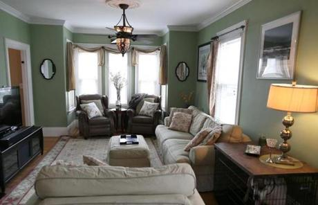 The Living Room In Light Green With White Crown Molding Runs The Length Of  The House